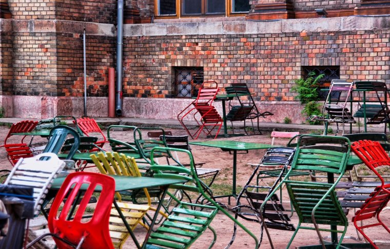 Colorful chairs propped up against tables in an open terrace