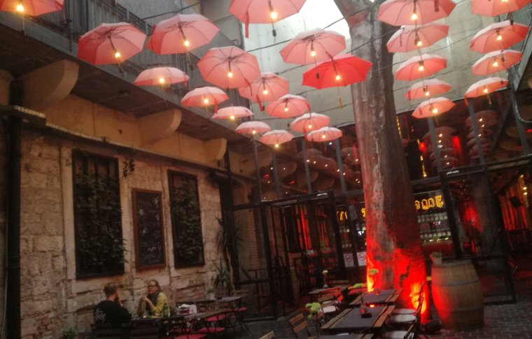 Lights made of umbrellas fill a roof area.