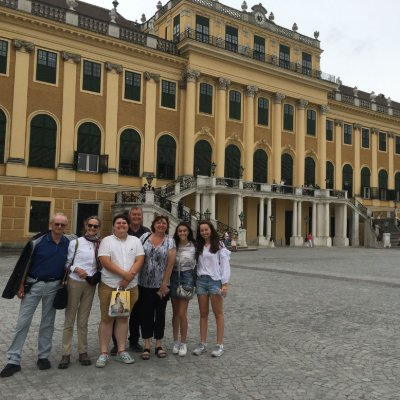 Group of smiling tourists in front of the Schonbrunn palace