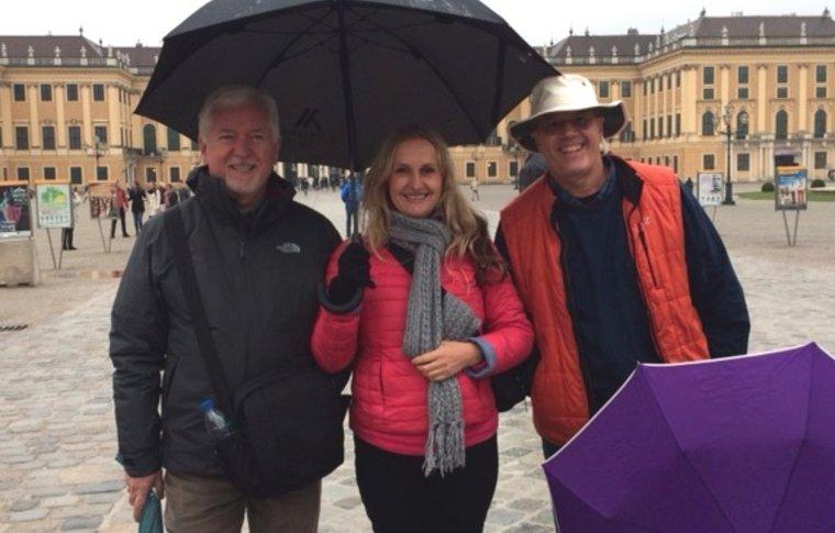 3 people smiling under umbrella