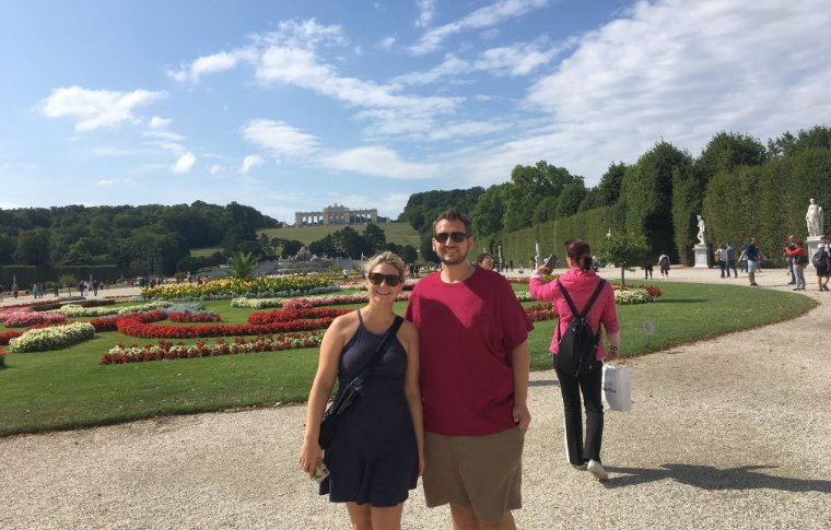 2 people smiling in front of large garden
