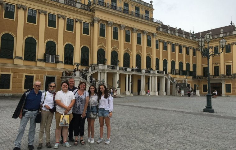 family smiling in front of large palace with yellow walls and many windows