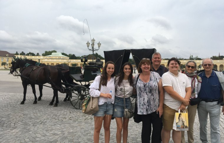 group of people smiling in front of horse and carriage
