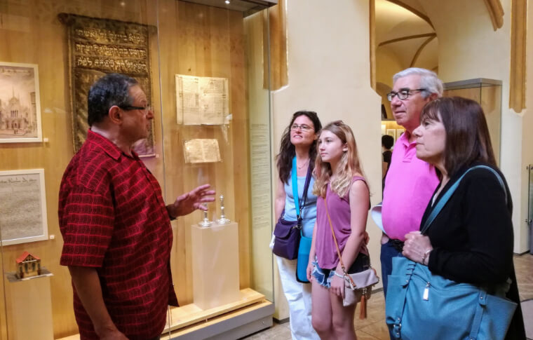 tour guide explaining old documents to group in museum