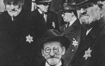 old black and white photo of men with star of david inscribed on their black coats