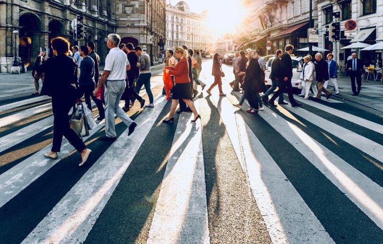 light shining through pedestrians crossing road