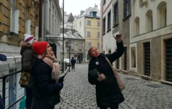 tour guide pointing up and explaning something on cobbled street