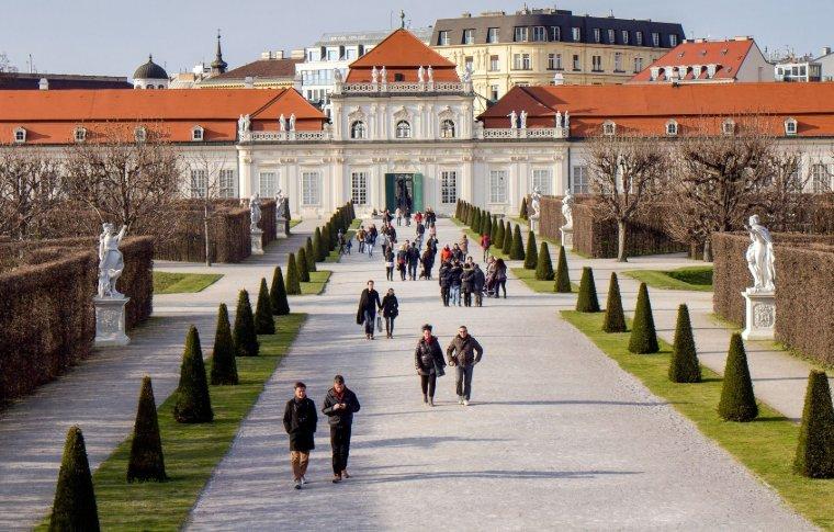 people walking along wide drive towards palace