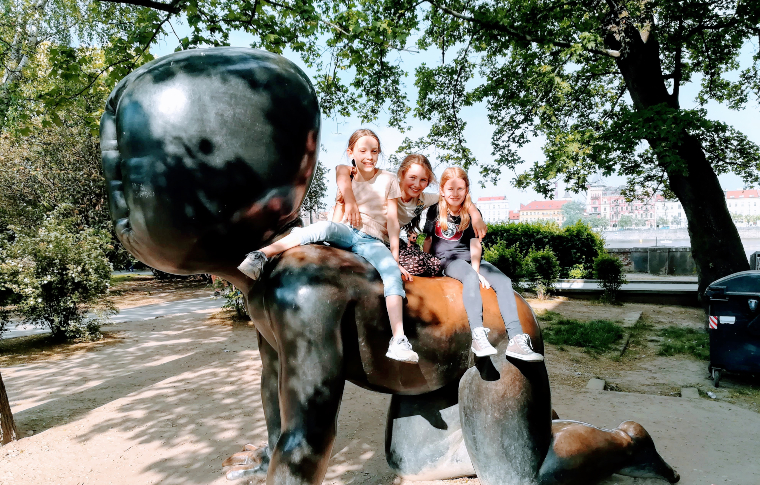 three girls smiling sitting on top of a baby sculpture