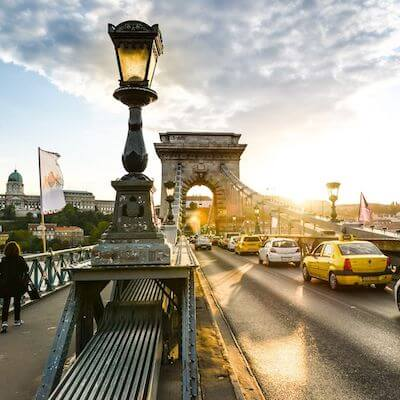 street lamps along bridge lit up by sunrise as cars cross over