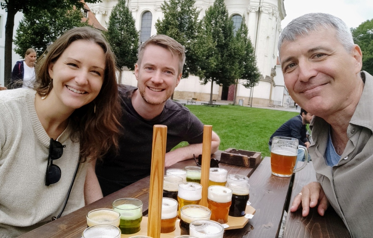 three people at a table tasting beer and smiling