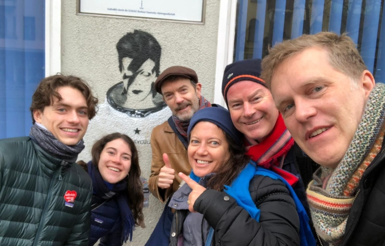 a tour group smiling in front of a David Bowie image on the wall