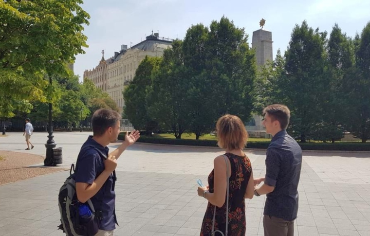 a guide and two tourists on Liberty Square in Budapest