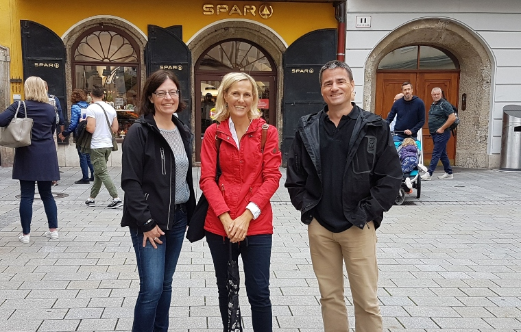 three people smiling on a paved street in Salzburg