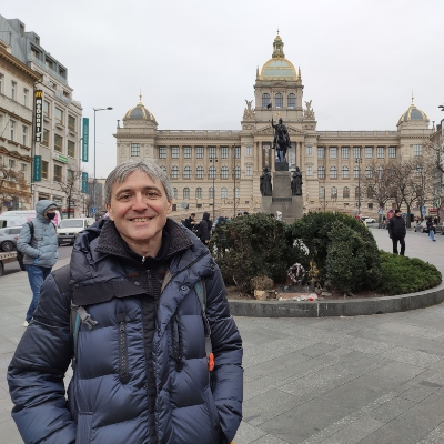 a man smiling in front of a fountain in the middle of a square