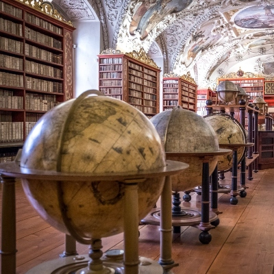 a row of old globes in the middle of a library hall
